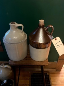 2 1-gallon crocks; solid one has couple of small nicks and hairline on spout; brown topped jug appears good condition